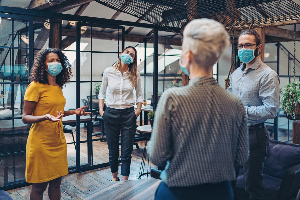 Group of entrepreneurs wearing masks and standing at a distance in the office